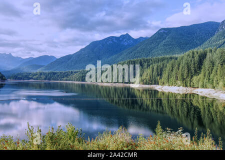 A scenic View of Cleveland Dam reservoir surrounded by mountains at sunset, North Vancouver, Canada