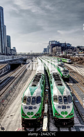 Toronto, Canada - March 20, 2019: Go trains stopping at a Railway station at sunny day - Stock Photo