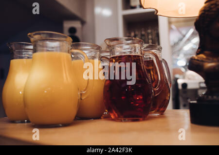 Several jars of fresh orange and berry juice on wooden table. Party concept. - Stock Photo