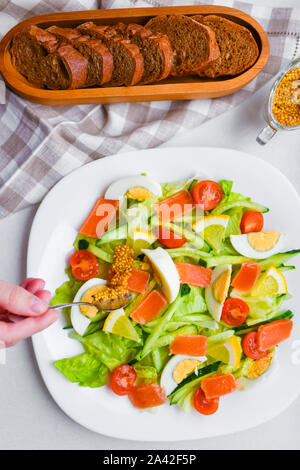 add mustard to vegetable salad. vegetable salad with human hands. on a white plate. add spices. - Stock Photo