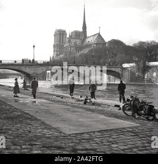 1950s, historical, parisian men fishing by the riverbank of the Seine at Pont de I'Archeveche, Paris, France, with the Notre-dame Catherdral in the background. Constructed in 1828, the 'Archbishop's Bridge' was built for the society 'Pont des Invalides' after the demolition of the suspension bridge at Les Invalides. - Stock Photo
