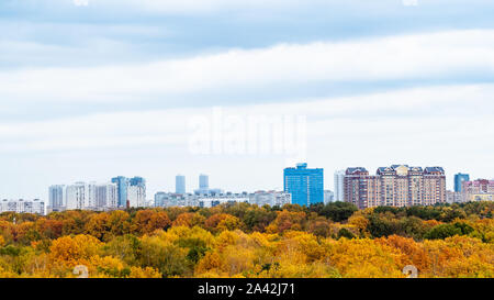 panoramic view of blue cloudy sky over city and yellow park on autumn day