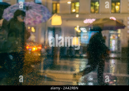 Rain on a window, looking out to people in a night street scene. Silhouettes of people with umbrellas - Stock Photo