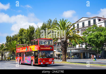 Funchal, Madeira, Portugal - Sep 10, 2019: Red double-decker tourist bus driving people around the Madeiran capital city. Hop on hop off buses, transport service. Tourist attraction. Vacation spot. - Stock Photo