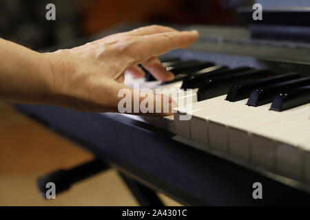 electric piano,  hand playing on the keyboard, fingers on the keys - Stock Photo