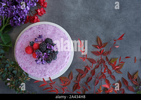 Ice cream cheesecake and berries on a background in green tones. Accompanied with a basket of blueberries, blackberries and raspberries.