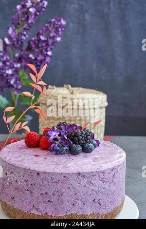 Ice cream cheesecake and berries on a background in green tones. Accompanied with a basket of blueberries, blackberries and raspberries. - Stock Photo