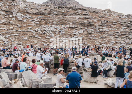 Delos, Greece - September 20, 2019: Large number of tourists watching performance at the ancient theatre on the Greek island of Delos, an archaeologic - Stock Photo