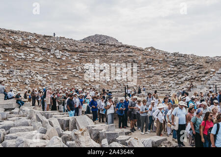 Delos, Greece - September 20, 2019: Large number of tourists leaving after performance at the ancient theatre on the Greek island of Delos, an archaeo - Stock Photo