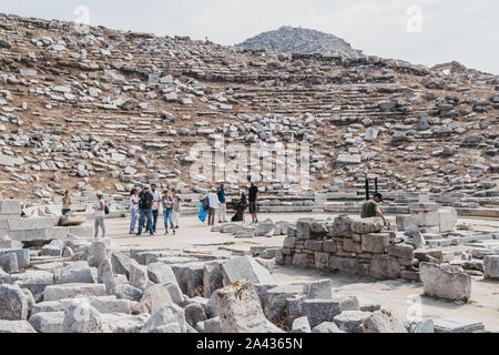 Delos, Greece - September 20, 2019: Tourists walking among ruins of ancient theatre on the Greek island of Delos, an archaeological site near Mykonos - Stock Photo