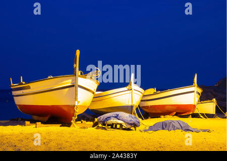 Three fishing boats on a sandy beach in the evening against the background of the sea. Lighting from lanterns, seashore in the Spanish city of Tossa d - Stock Photo