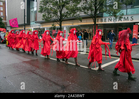 London, UK - 11 October 2019. The Red Rebel Brigade  from Extinction Rebellion dressed in red to represent the blood of 1000 or more dead or dying animal and plant species walk in a line on Oxford Street  on the fifth day of climate protests  as part of a campaign to force the government to declare a climate emergency and a commitment to halting loss of biodiversity and net zero carbon emissions by 2025 and for the creation of a Citizens' Assembly on climate and ecological justice. Credit: amer ghazzal/Alamy Live News - Stock Photo
