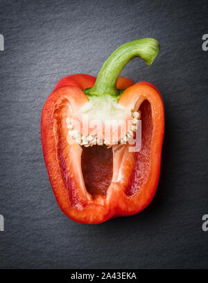 Red cut sweet pepper half on stone. - Stock Photo