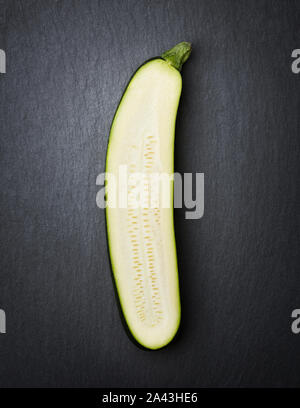 One sliced courgette isolated on stone. - Stock Photo
