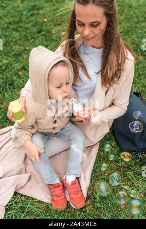 mom woman sits in park on grass little boy son 3 5 years old blowing air soap bubbles happy smiling laughing resting having fun autumn city 2a43mc6