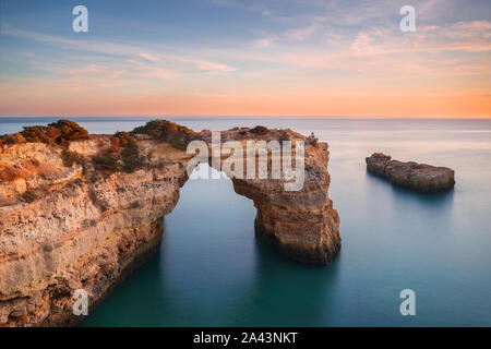 Algarve beach, romantic couple watching the sunset. Loving moment under natural arch carved in stone is a tourist attraction of the south coast of Por - Stock Photo