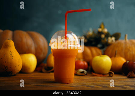 Pumpkins juice in bottles with pumpkins. Glass of fresh pumpkin smoothie on wooden background - Stock Photo