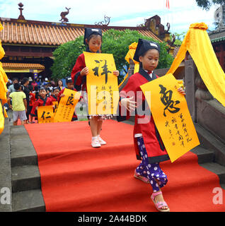 Over 30 pre-school children dressed in traditional Han-style costumes attend their 'first writing' ceremony at the Chinese Confucius Temple School in - Stock Photo