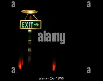 Green exit sign under lamp on a post in a cozy comfortable dim place - Stock Photo
