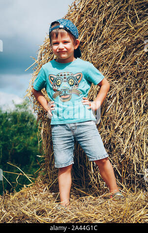 A little boy in a blue baseball cap and short denim shorts plays on straw bales on a hot summer day - Stock Photo