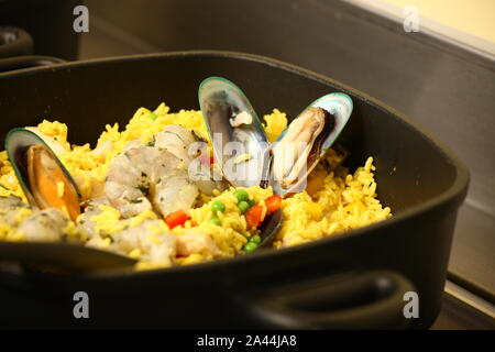 oysters in rice being cooked in a pan - Stock Photo