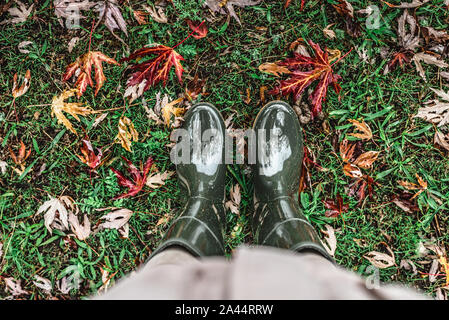 Feet in olive green rubber boots standing on green grass with fallen autumn leaves. Stock Photo