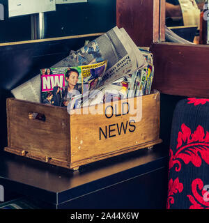 Gold Coast, Queensland/Australia - Feb 27, 2016: Wooden tray with text Old News on it and old magazines and newspapers. Concept of old news, obsolete - Stock Photo