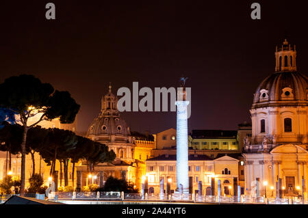 A monument from 113 AD Trajan's Column survives intact in the ruins of Trajan's Forum at night in Rome Italy across from Santa Maria di Loreto. Stock Photo