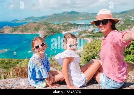 Family taking selfie enjoying the view of picturesque English Harbour at Antigua. View of paradise bay at tropical island in the Caribbean Sea. Family - Stock Photo
