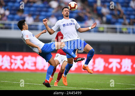 German football player Sandro Wagner of Tianjin TEDA F.C., right, stops the ball with his chest during the 21st round of Chinese Football Association - Stock Photo