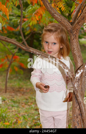 Adorable baby girl holds snail, playing in a sunny park under a tree with yellow leaves, hiding behind tree - Stock Photo