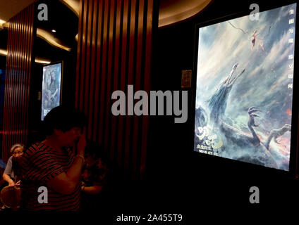 A Chinese filmgoer waits in front of a poster of Chinese animated film 'Ne Zha' at a cinema in Yichang city, central China's Hubei province, 6 August - Stock Photo