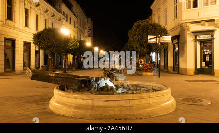 GYOR, HUNGARY 08 10 2019 : Statue of man rowing on a boat in the hungarian city Gyor at night - Stock Photo