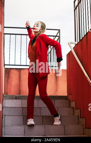 young woman with Joker makeup and costume, dancing on steps - Stock Photo
