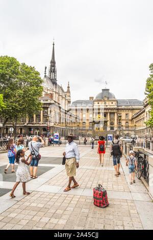 tourists taking photographs  on ile de la cite with palais de justice in background