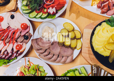 Food tray with delicious salami, pieces of sliced ham, sausage and salad. Meat platter with selection on table - Stock Photo