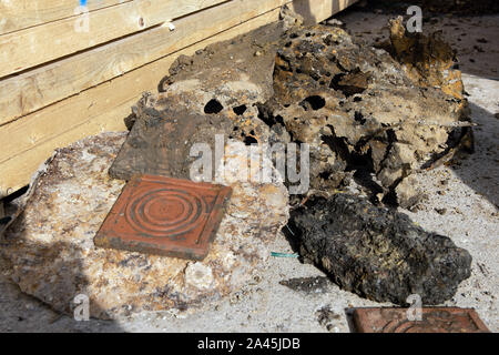 12 October 2019, Lower Saxony, Göttingen: Remains of tin barrels, slag and clay bricks, which were found on a heap in the ground and were originally suspected of being a world war bomb, lie next to wooden pillars. In the morning about 14,000 people were evacuated around the site. Photo: Swen Pförtner/dpa - Stock Photo