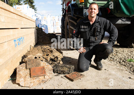 12 October 2019, Lower Saxony, Göttingen: Thorsten Lüdeke, demolition engineer of the Lower Saxony Explosive Ordnance Removal Service, sits next to remains of metal drums, slag and clay bricks found on a heap in the ground and originally suspected of being a world war bomb. In the morning about 14,000 people were evacuated around the site. Photo: Swen Pförtner/dpa - Stock Photo