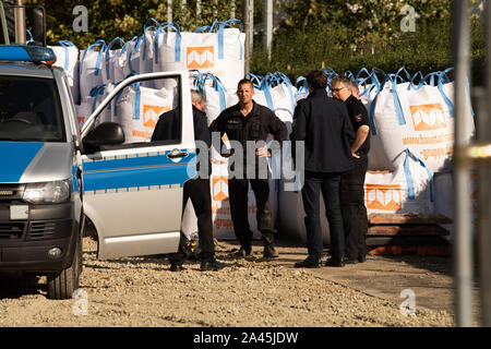 12 October 2019, Lower Saxony, Göttingen: Thorsten Lüdeke (M), demolition engineer of the Lower Saxony Explosive Ordnance Removal Service, stands with colleagues at the site where the remains of metal drums, slag and clay bricks were found, which were found on a heap in the ground and were originally suspected as a world war bomb. In the morning about 14,000 people were evacuated around the site. Photo: Swen Pförtner/dpa - Stock Photo