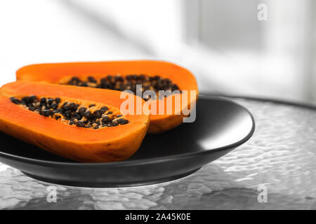Two half of ripe papaya with seeds in a black plate on a glass table with a white background. Slices of sweet papaya. Halved papayas. Healthy exotic - Stock Photo