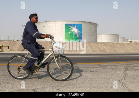 Abqaiq, Saudi Arabia. 12th Oct, 2019. EASTERN PROVINCE, SAUDI ARABIA - OCTOBER 12, 2019: A worker rides a bicycle by oil tanks at an oil processing facility of Saudi Aramco, a Saudi Arabian state-owned oil and gas company, at the Abqaiq oil field. On 14 September 2019, two of the major Saudi oil facilities, Abqaiq and Khurais, suffered massive attacks of explosive-laden drones and cruise missiles; the Houthi movement, also known as Ansar Allah, claimed responsibility for the attacks. Stanislav Krasilnikov/TASS Credit: ITAR-TASS News Agency/Alamy Live News - Stock Photo
