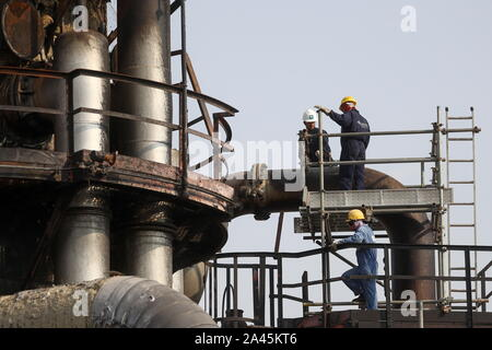 Abqaiq, Saudi Arabia. 12th Oct, 2019. EASTERN PROVINCE, SAUDI ARABIA - OCTOBER 12, 2019: Workers by damaged objects at an oil processing facility of Saudi Aramco, a Saudi Arabian state-owned oil and gas company, at the Abqaiq oil field. On 14 September 2019, two of the major Saudi oil facilities, Abqaiq and Khurais, suffered massive attacks of explosive-laden drones and cruise missiles; the Houthi movement, also known as Ansar Allah, claimed responsibility for the attacks. Stanislav Krasilnikov/TASS Credit: ITAR-TASS News Agency/Alamy Live News - Stock Photo