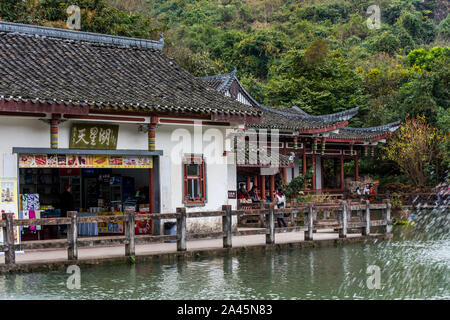 Gift shops in the Chinese ancient house with The Tianxing lake and fountain, in the National park of Huangguoshu waterfall, in Guizhou province of Chi - Stock Photo