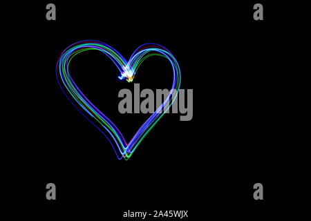 Long exposure photograph off a heart shape symbol in vibrant multi color light against a black background. Light painting photography. - Stock Photo