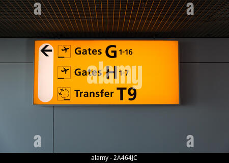 Yellow illuminated sign at airport with gate and transfer desk numbers for departing flights - Stock Photo