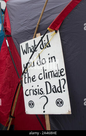 London, UK. 11 October 2019. Banner on a tent at the Extinction Rebellion camp at Trafalgar Square saying 'What did you do in the climate crisis dad?'. Climate change protesters, Extinction Rebellion, were still occupying Trafalgar Square despite many of their campsites around Westminster being removed by police. The group have been involved in non-violent civil disobedience. One of Extinction Rebellion's main demands is to reduce greenhouse gases to net zero by 2025. Over 1,000 arrests were made in the first week of protests. Stuart Walden / Alamy - Stock Photo