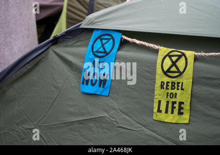 London, UK. 11 October 2019. Banners on a tent at Trafalgar Square. Climate change protesters, Extinction Rebellion, were still occupying Trafalgar Square despite many of their campsites around Westminster being removed by police. The group have been involved in non-violent civil disobedience. One of Extinction Rebellion's main demands is to reduce greenhouse gases to net zero by 2025. Over 1,000 arrests were made in the first week of protests. 500 officers were drafted in from around England and Wales to help support the Metropolitan police. Stuart Walden / Alamy - Stock Photo