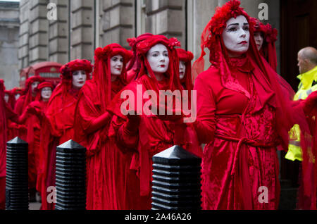 London, UK. 11 October 2019. Red-robed, Climate change protesters, The Red Brigade, from Extinction Rebellion walk along Whitehall in London. By day 5 protestors, still occupied Trafalgar Square despite many of their campsites around Westminster being removed by police. One of Extinction Rebellion's main demands is to reduce greenhouse gases to net zero by 2025. Over 1,000 arrests were made in the first week. 500 officers were drafted in from around England and Wales to help support the Metropolitan police. Stuart Walden / Alamy - Stock Photo