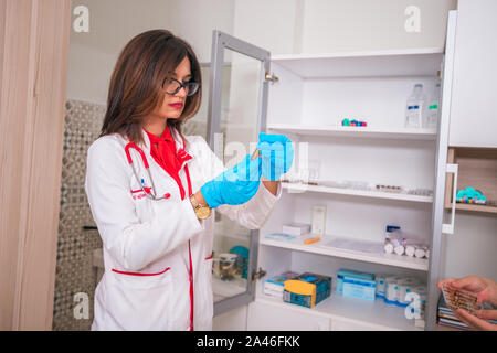 Doctor ( nurse ) holding a syringe while standing in a medical office - Stock Photo