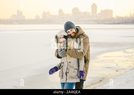 Young couple cheerfully flounders in snow. Between comic fight. Happy young couple hugs in winter snowy woods. Romantic lifestyle men and women in - Stock Photo